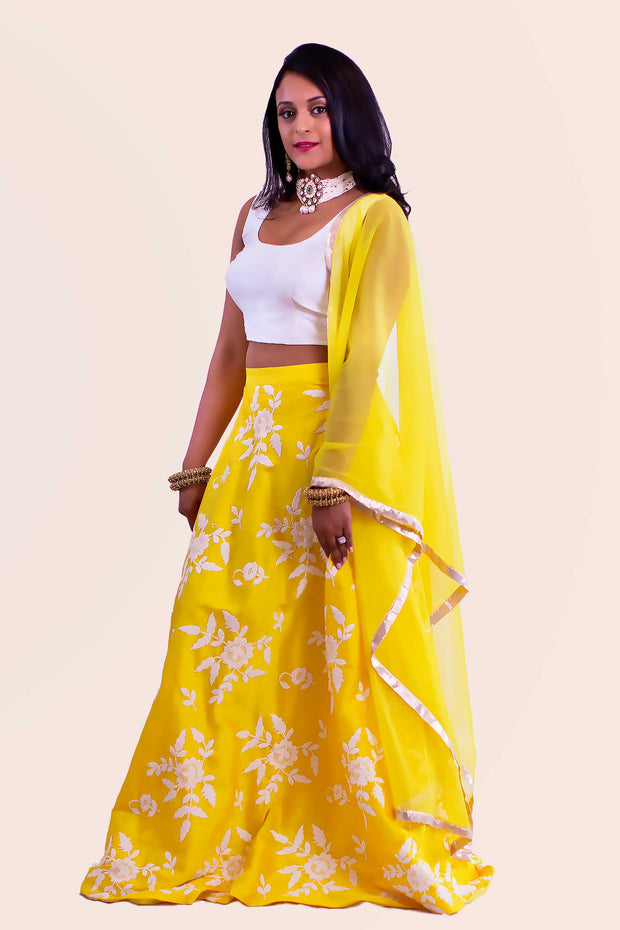 Coy two piece yellow lehenga with luscious white flowers threaded on skirt. Paired with simple modern blouse. Finish this look with yellow chiffon dupatta decorated with gold trim on shoulders/ shoulder.