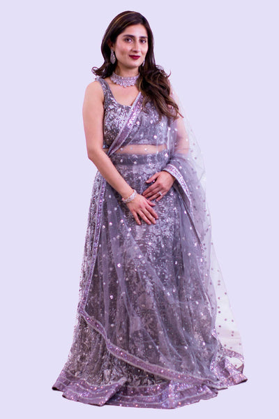 Vivacious light purple lehenga, covered In Swarovski crystals on skirt and blouse. Heavy embroidery pattern of breathtaking flowers and crystals. Finish this look by draping the light purple dupatta with matching border as skirt on shoulders/ shoulder.
