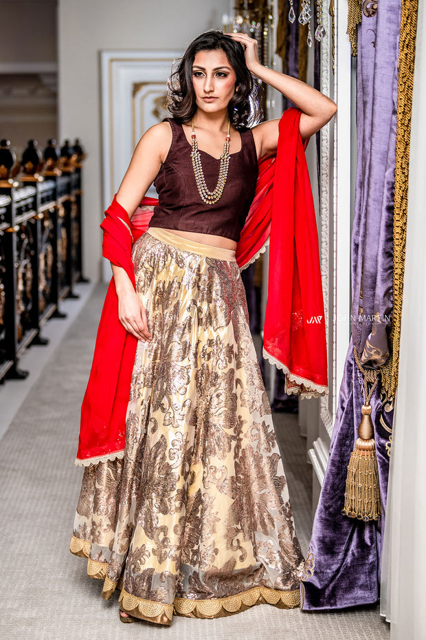 Radiant two piece lehenga, paired with deep chocolate blouse. Beige skirt covered in copper and gold metallic embroidery. Finish this look by draping color blocking red dupatta on shoulders/ shoulder.