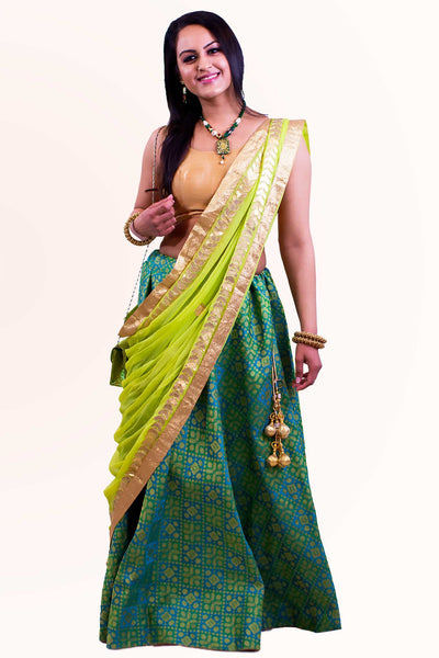 Sparkling two piece lehenga, skirt covered in beautiful teal silk work, paired with gold blouse. Finish this look by draping light kiwi green chiffon dupatta decked in gold border on shoulders/shoulder.