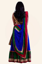 Colorful two piece lehenga with blue skirt finished with green and gold border covered in red and blue followers. Paired with gold blouse. Finish this colorful look by draping color blocking dupatta in red and green on shoulders/ shoulder.
