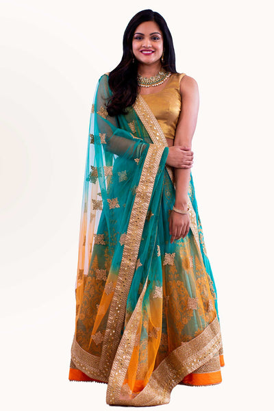 Breathe taking tropical lehenga, skirt consisting of true toned teal and orange gold border. Decadent gold embroidery on skirt and long sleeved blouse for refined appeal. Finish this look by draping heavy chiffon color blocking dupatta, thick gold border on shoulders/ shoulder.