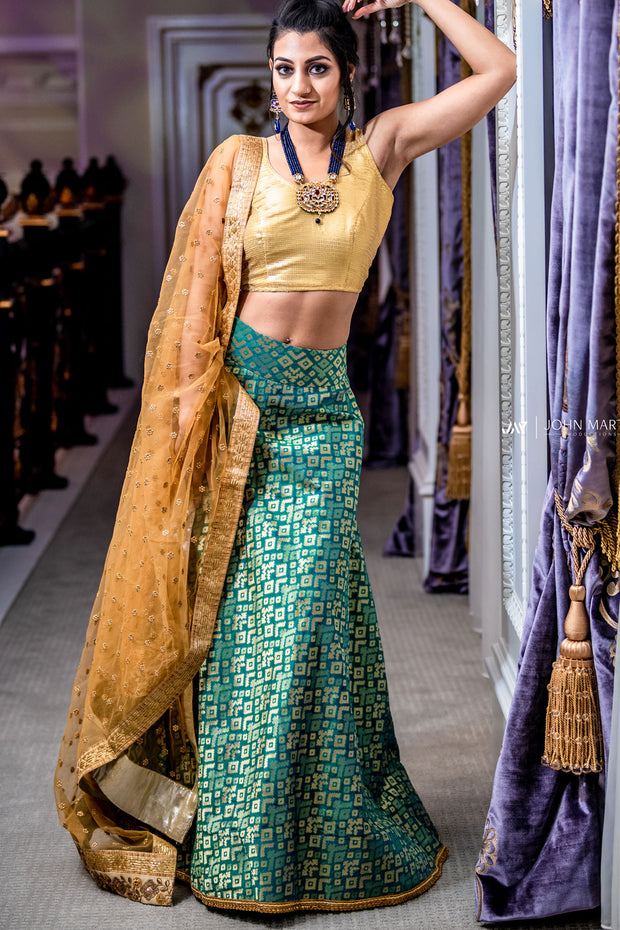 Sparkly two piece lehenga with green silk skirt covered in metallic design. Paired with radiant white silk blouse. Finish this look by draping the gold dupatta with flower trim and gold border on shoulders/ shoulder.