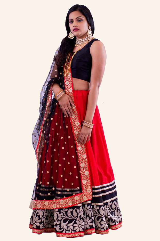 Red two piece lehenga with black blouse. Red skirt with heavy flower gold embroidery with golden glitter trim. Finish this look by draping matching red and black border dupatta on shoulders/ shoulder.