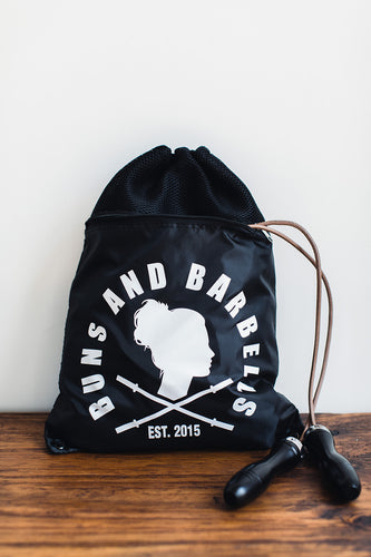 Black drawstring backpack with athletic gear