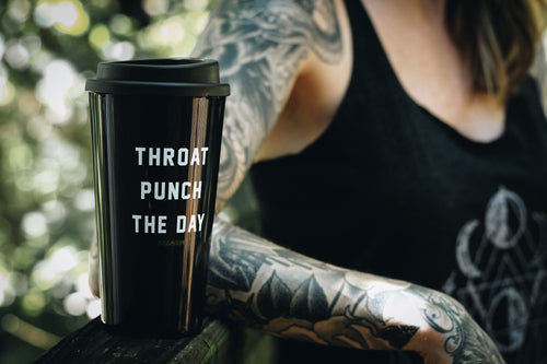 tattooed woman sitting outside with a black travel mug that says throat punch the day