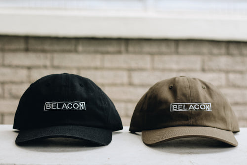 black and olive hats sitting on ledge
