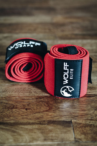 red wrist wraps laying on a hardwood floor