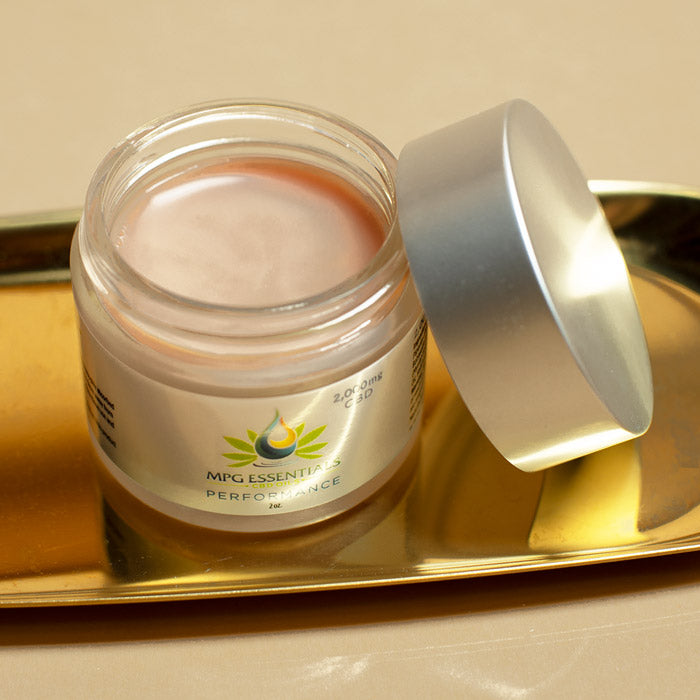 open container of CBD salve on gold tray