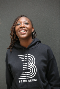 Woman wearing black hoodie with 'B' and 'Be The Bridge' in white lettering.