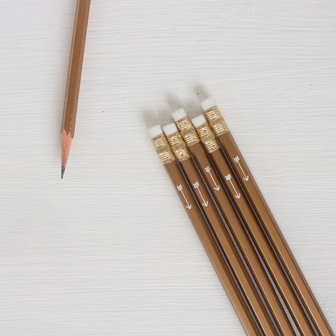 gold pencils with white arrow