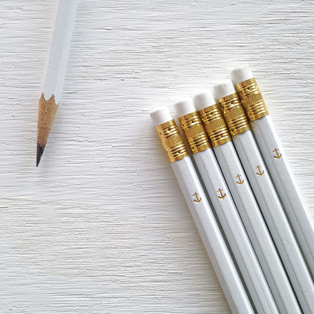 white pencils with gold anchor