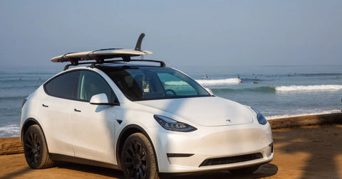 Tesla Model Y with a surfboard mounted on the roof rack
