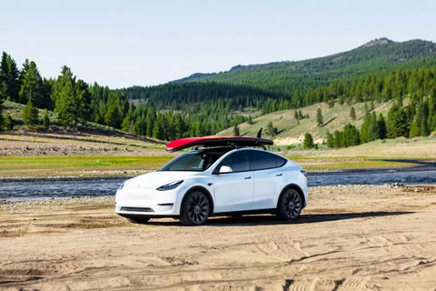 Tesla Model Y with a padd board mounted on the roof rack