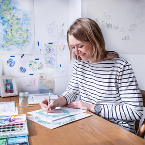 Polly painting at her desk with watercolours