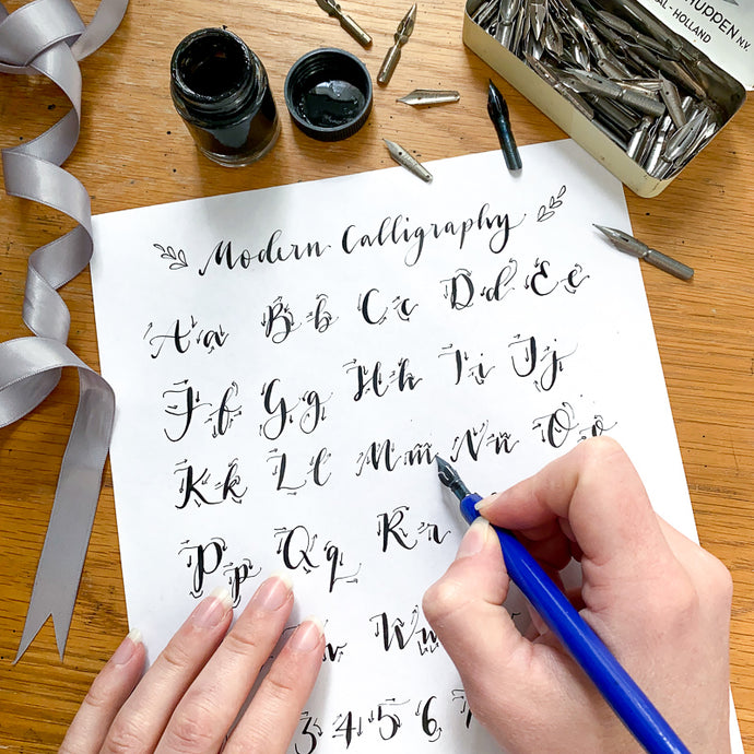 Calligraphy guide sheet with hand holding a nib