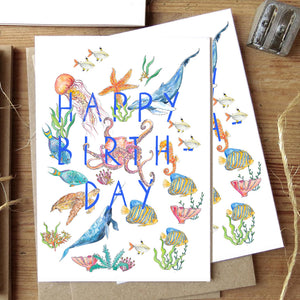 Happy birthday greetings card with underwater animals and fish flatlay