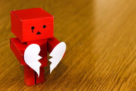 Small paper red robot on a wooden surface holding a white paper heart torn in half. There is also a tear drawn on the robot's face coming from its right eye and a frown on its face.