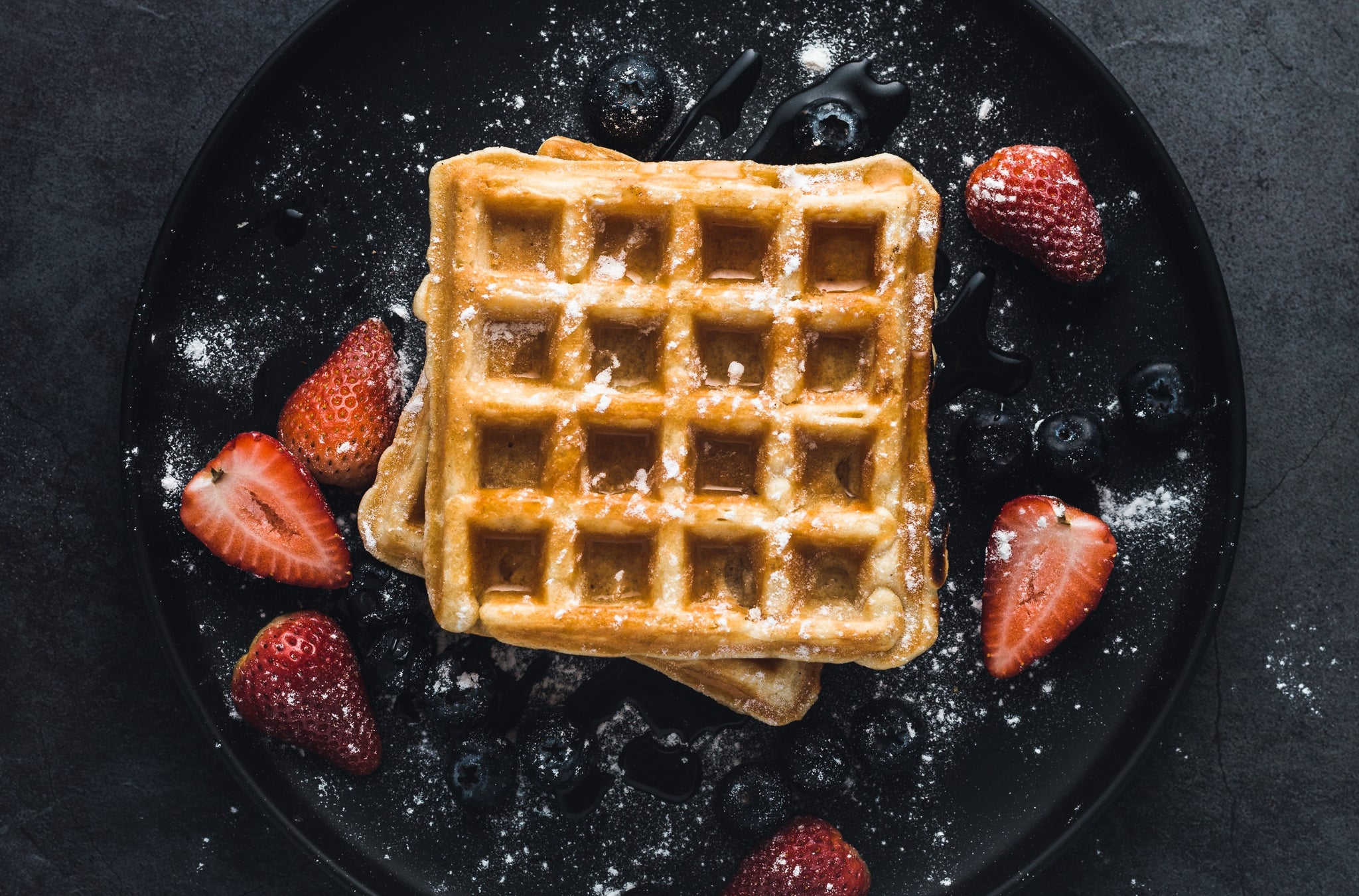 Two square waffles stacked on top of each other on a black plate shown from above, sprinkled with powdered sugar and several strawberries slices in half also laying on the plate.