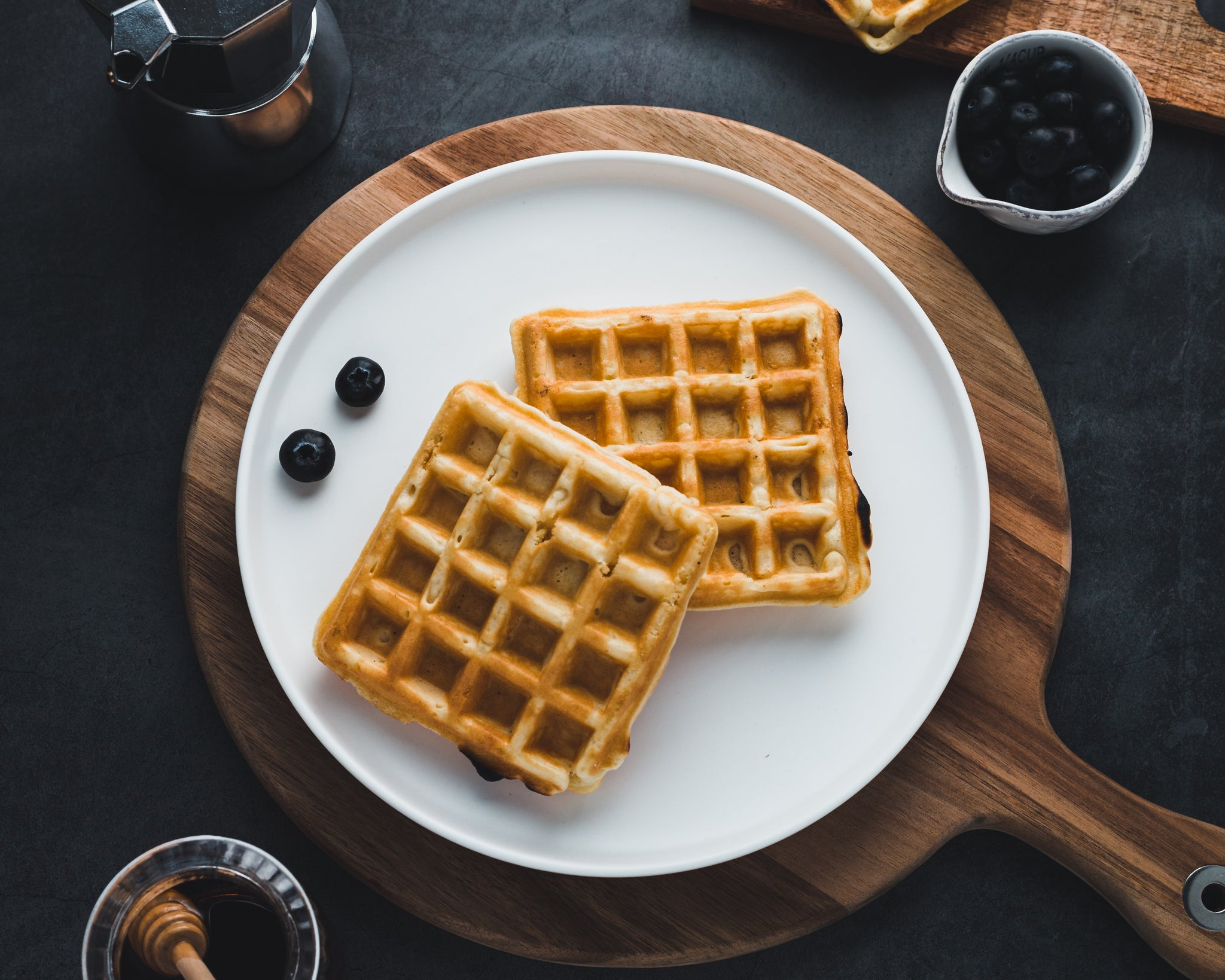 Two plain square waffles on round white plate with two blueberries to the left of waffles. Round white plate is sitting on top of a brown circular wooden pizza paddle.