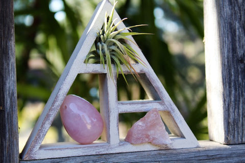 rose quartz yoni egg and raw rose quartz crystal in triangle