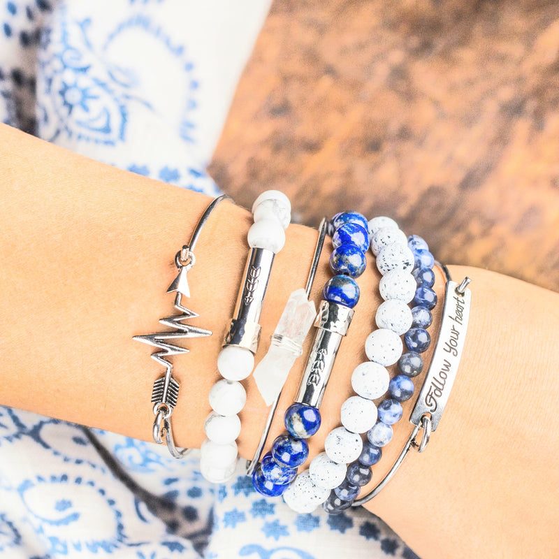 Womans wrist with blue, silver, and white bracelet stack. Beaded white howlite with silver clasp intention bracelet, beaded blue lapis with silver clasp intention bracelet, beaded white lava stone with silver clasp intention bracelet, silver and clear Quartz triple bangles set that reads 'Follow Your Heart'