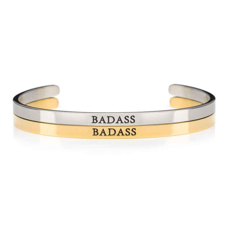 1 silver and 1 gold open cuff bracelet that say BADASS in black lettering