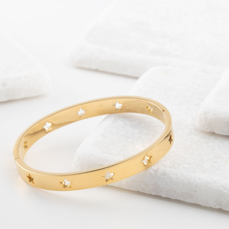 Gold bangle bracelet with star cutouts all around