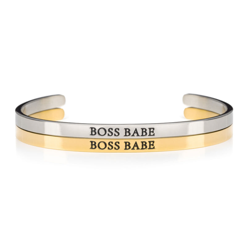 1 silver and 1 gold open cuff bracelet that say BOSS BABE on black lettering