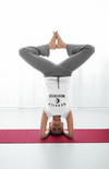 Women in headstand, wearing white t-shirt with black HEAVILY MEDITATED graphic and a black moon in the center