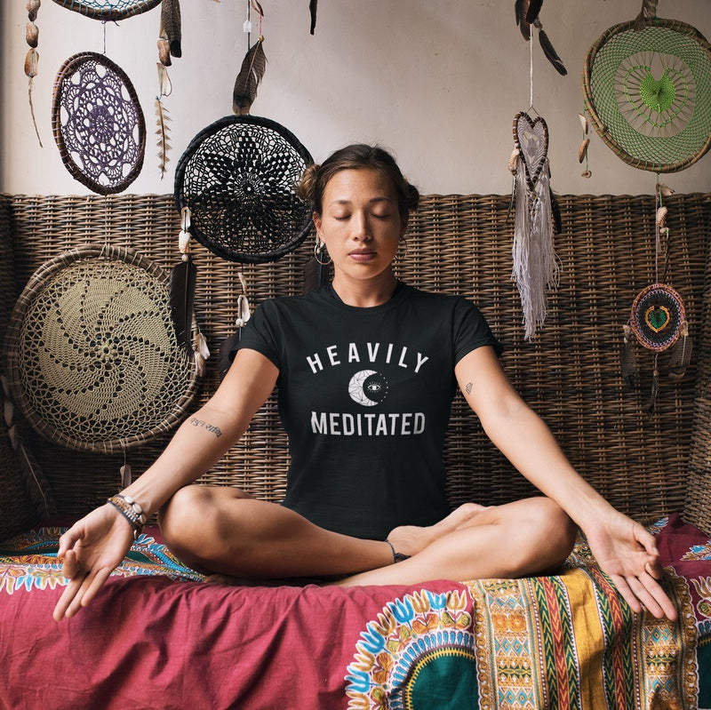 Women meditating wearing black t-shirt with white HEAVILY MEDITATED graphic and a white moon in the center