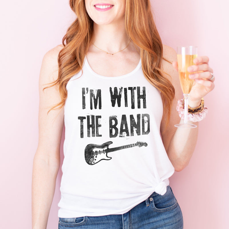 Woman holding champagne, wearing a white rocker racerback tank top with  a distressed  black guitar graphic on the front, and distressed black lettering that says 'I'M WITH THE BAND'