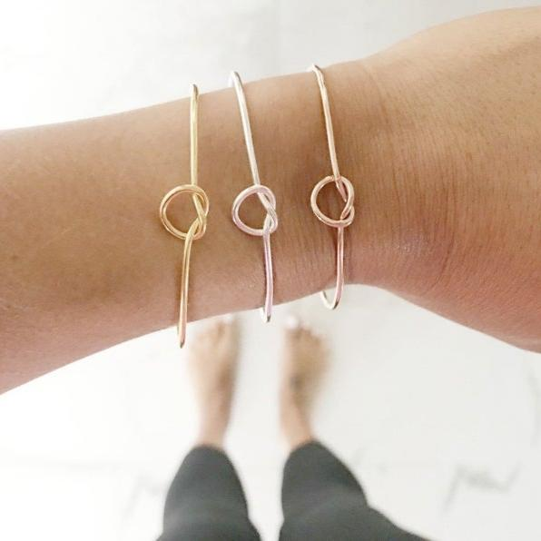 3 knot bracelets on womans wrist: gold, silver and rose gold