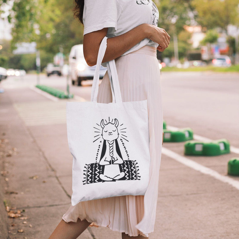 White canvas tote bag with black graphic of a meditating llama sitting cross-legged doing yoga