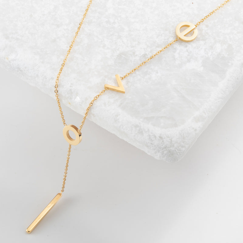 "Gold lariat necklace with lowercase latters spelling ""love"""