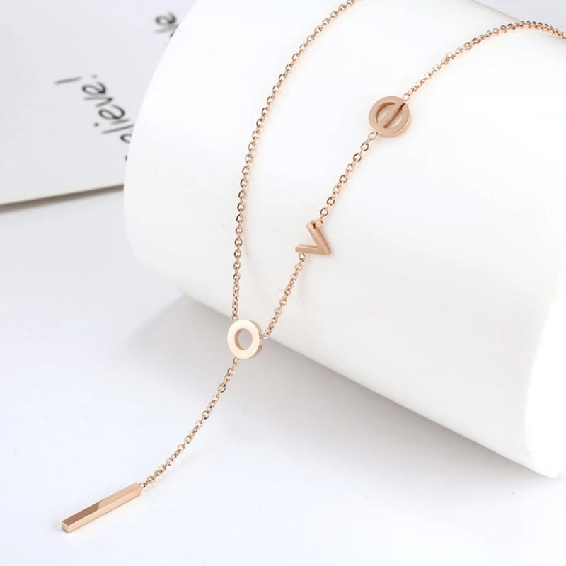"Rose Gold lariat necklace with lowercase latters spelling ""love"" with the letter ""l"" hanging down the center"
