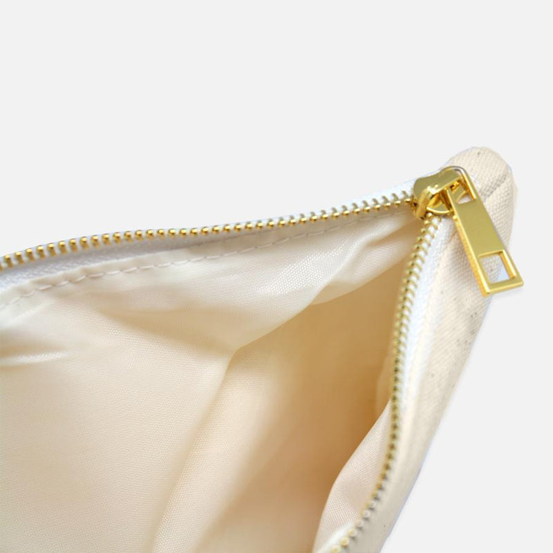 Gold zipper on white canvas cosmetic bag