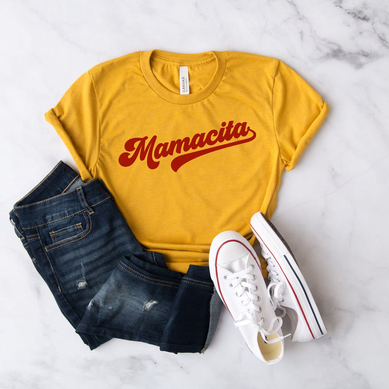 Yellow t-shirt with red cursive mamacita graphic paired with jeans and white sneakers
