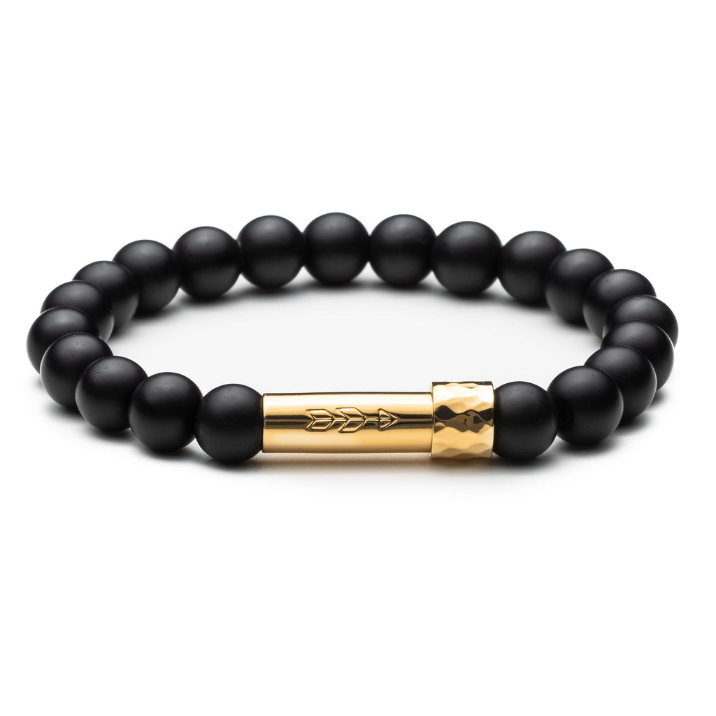 Matte black onyx gemstone beaded intention bracelet with gold cylinder clasp that unscrews to hold a scroll of paper. Clasp features a handstamped arrow.