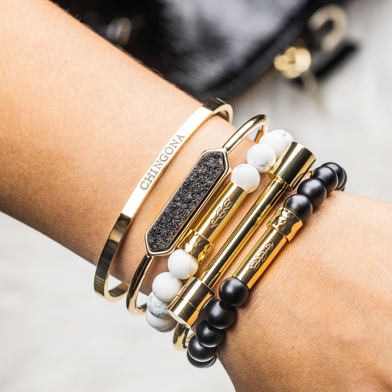 Black, white, and gold bracelet stack on woman's wrist. Gold Chingona cuff bracelet, black druzy gold cuff bracelet, white howlite beaded intention bracelet with gold clasp, gold screw-on bar shackle bracelet, matte black onyx beaded intention bracelet with shiny gold clasp