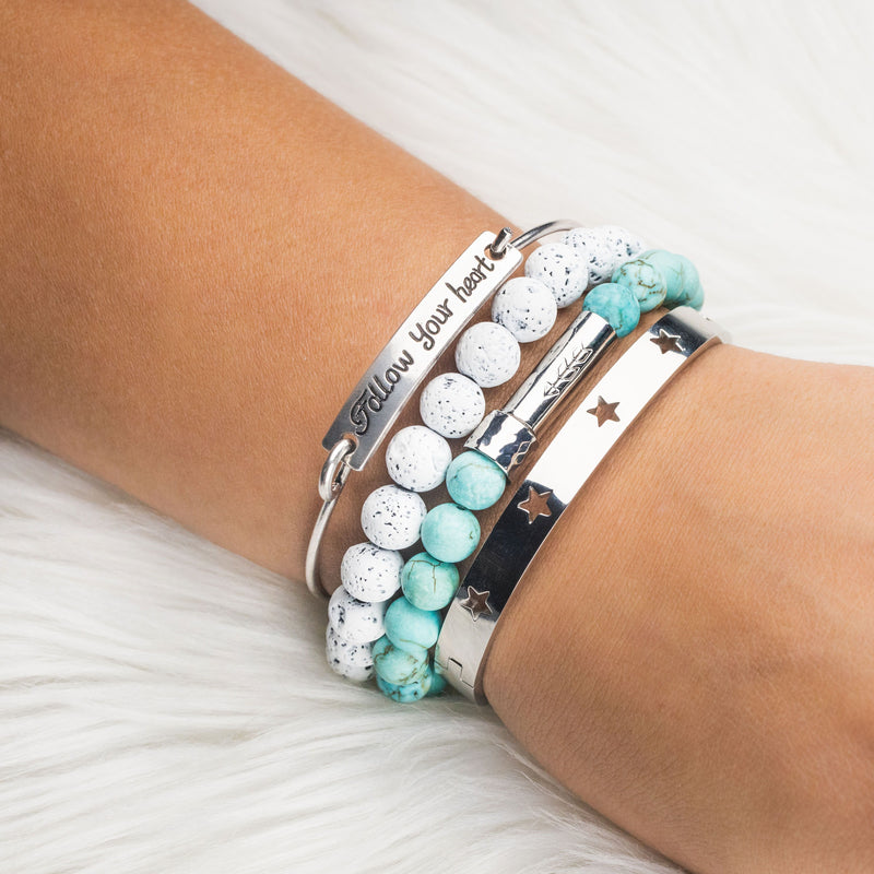 Womans arm with stack of bracelets in white, turquoise and silver. 1 silver bangle with the words 'Follow Your Heart', 1 silver bangle with star cutouts, 1 white lava stone beaded intention bracelet, and 1 matte turquoise beaded intention bracelet. Both intention bracelets have silver cylinder clasps with handstamped arrow. Clasps unscrew open to hold a scroll of paper inside to write a mantra or goal.