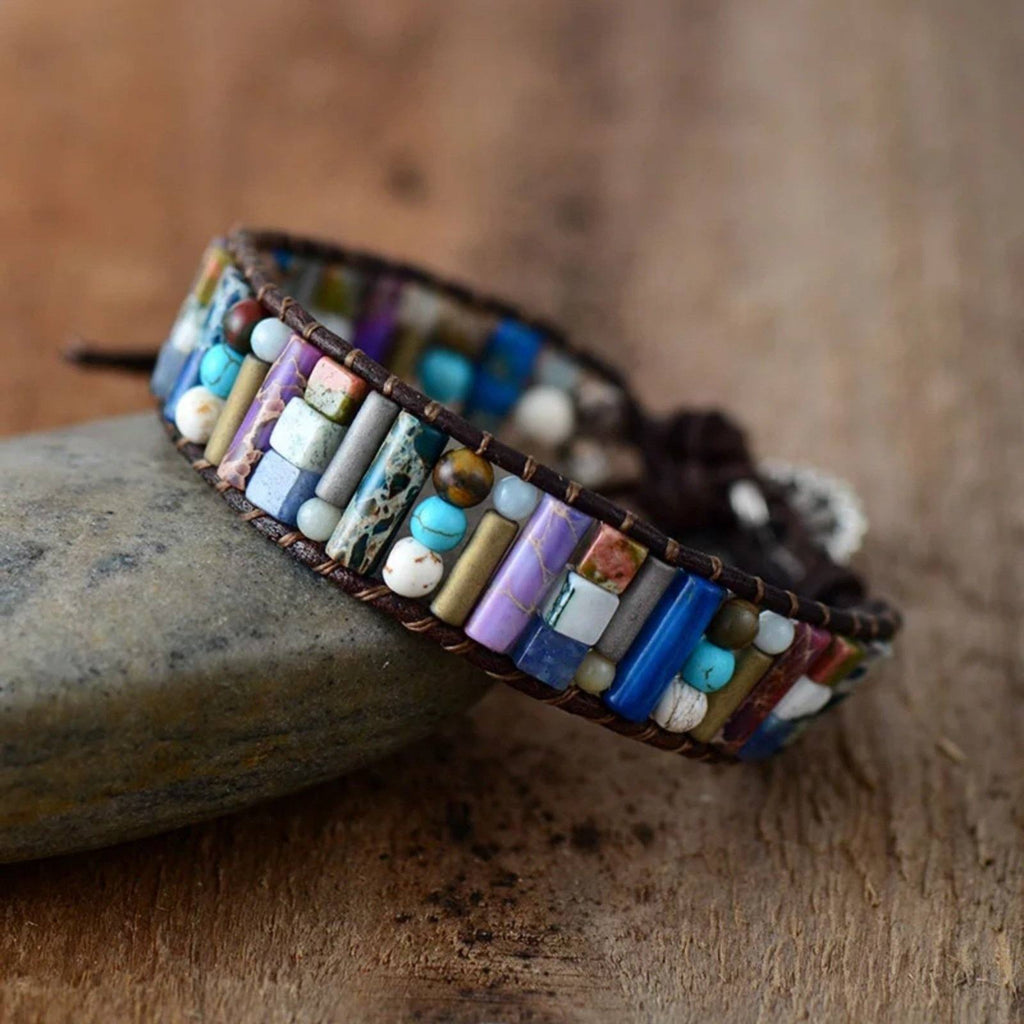 Multi-colored jasper and agate gemstone beaded bracelet on dark brown leather cording, leaning on a rock