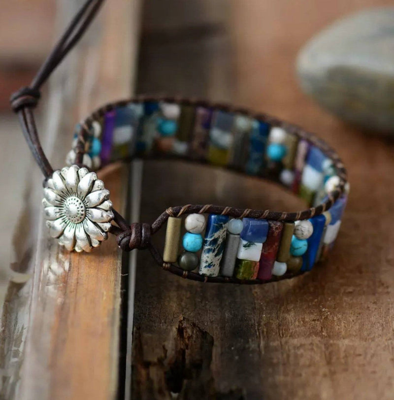 Multi-colored gemstone beaded chakra bracelet made with dark brown leather cord with silver sunflower button closure