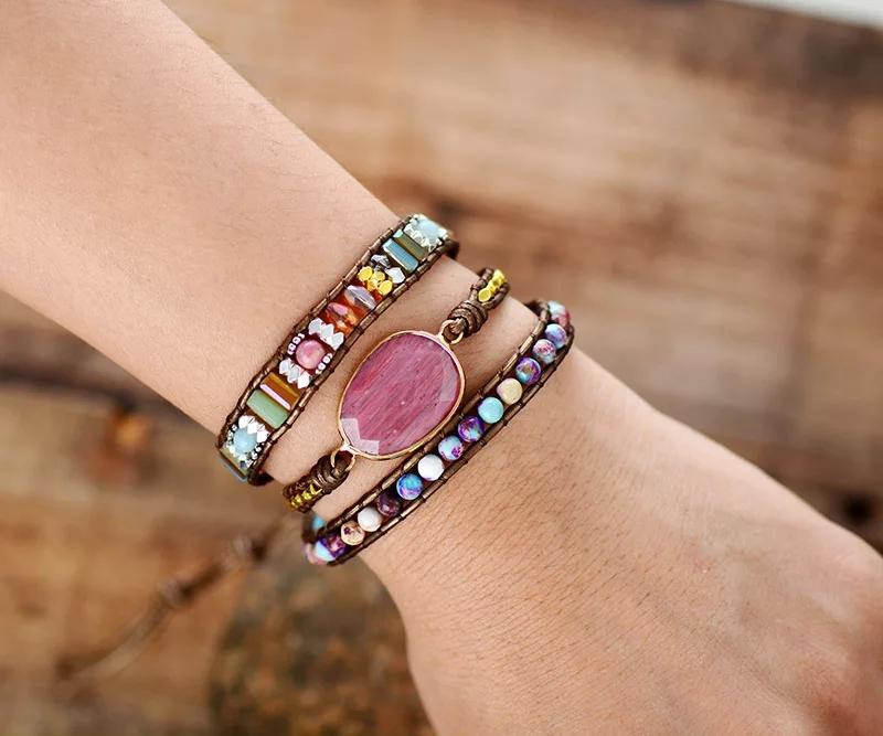 Leather boho wrap bracelet with large pink rhodonite gemstone centerpiece and pink, purple, and metallic beads