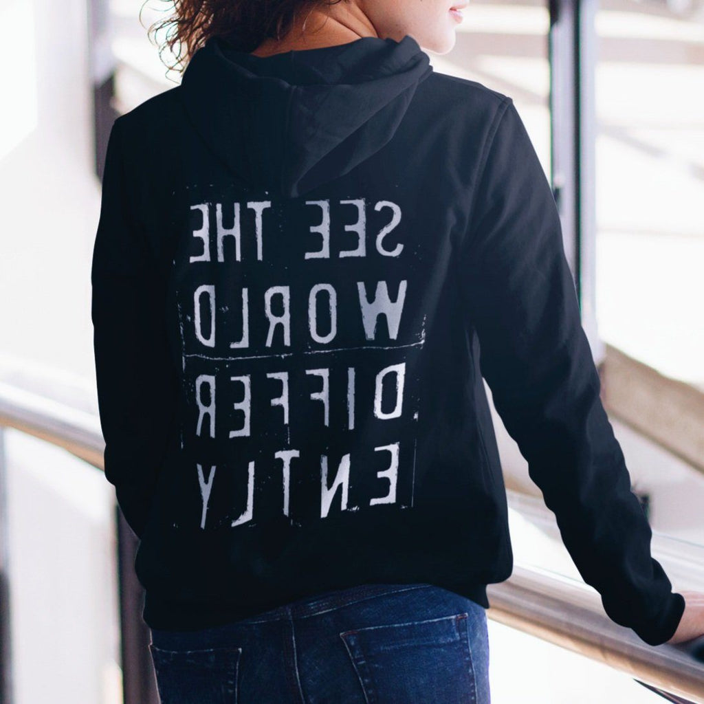 Woman wearing black hooded sweatshirt with the words 'See The World Differently' printed backwards on the back in reverse white lettering