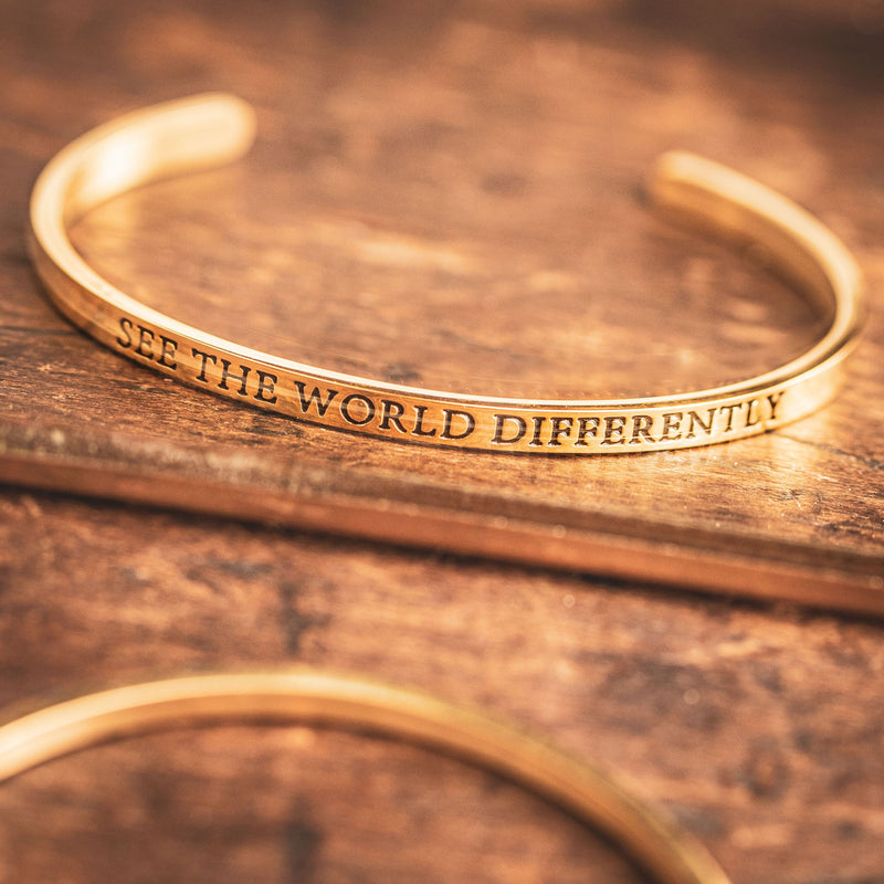 1 gold cuff bangle bracelet shown in mirror, with the worde SEE THE WORLD DIFFERENTLY printed backwards in black