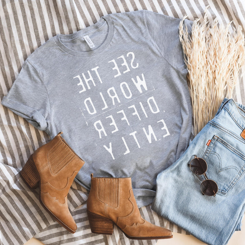 Heather Gray T-shirt with reverse white letters that say See The World Differently backwards