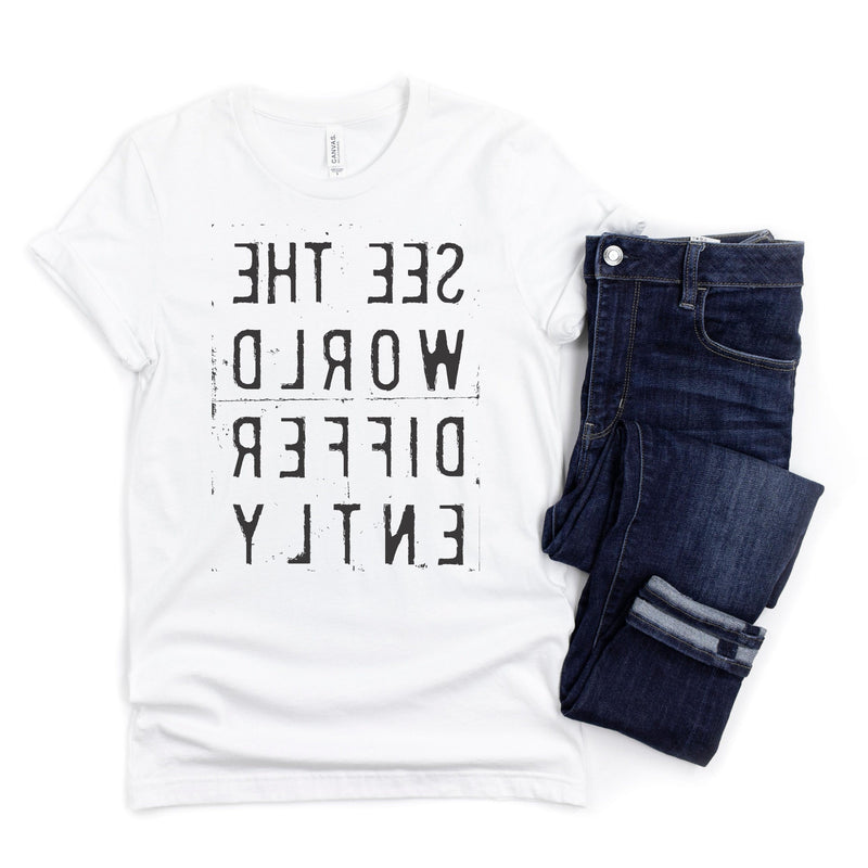 White T-shirt with reverse black letters that say See The World Differently backwards