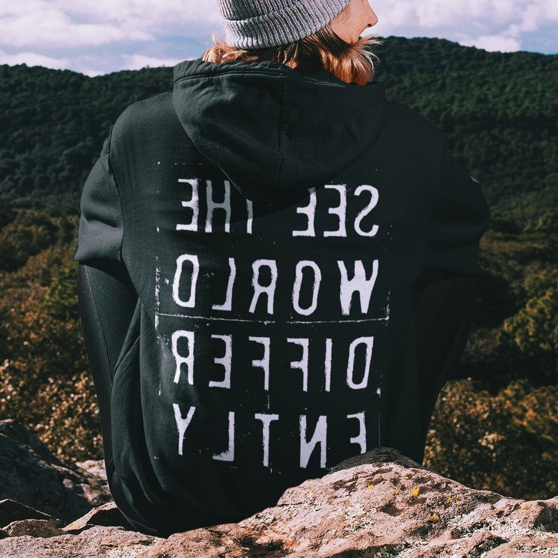 Sitting woman wearing black hooded sweatshirt with the words 'See The World Differently' printed backwards on the back in reverse white lettering