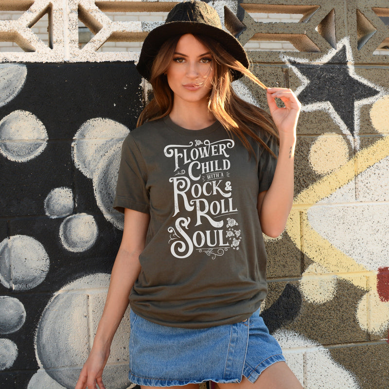 Woman wearinf army green T-shirt with distressed white Flower Child With A Rock and Roll Soul graphic